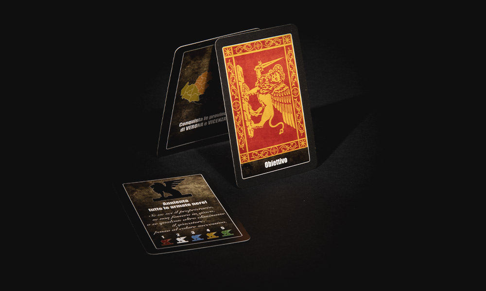 """Nel gioco da tavolo La Baruffa Veneta basato sulla regione Veneto, le """"carte obiettivo"""" rappresentano gli obiettivi da raggiungere per vincere la partita. Nell'immagine tra carte obiettivo con il dettaglio del retro della carta con il leone marciano di Venezia su sfondo rosso."""