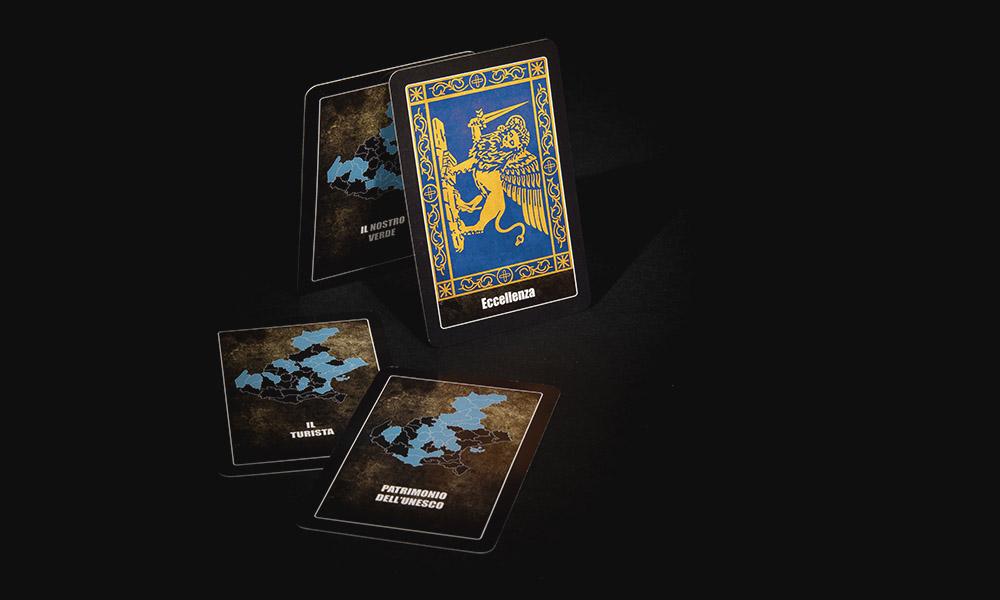 """La Baruffa Veneta, gioco di strategia basato sulla Regione Veneto. Nella modalità di gioco con le """"Carte Eccellenza"""", ogni carta rappresenta l'obiettivo da raggiungere. Nell'immagine ci sono quattro carte eccellenza con il dettaglio del retro delle carte con la raffigurazione del Leone Marciano o Leone di San Marco, simbolo di Venezia, su sfondo blu."""